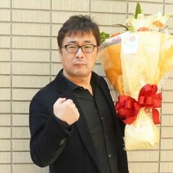 学生から贈られた花束を片手にファイティングポーズを取る常見氏