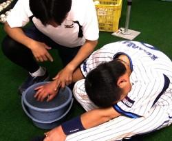 親指にデッドボールを受け、ダグアウトで治療する黒羽根捕手の様子(C)YDB