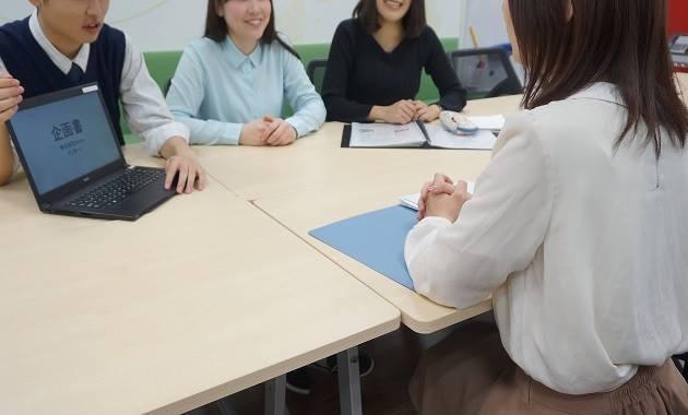 クライアント企業に自分たちで考えた企画を提案する学生たち