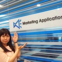 平成広報女子会所属の重光綾香。MApps社のロゴの前で