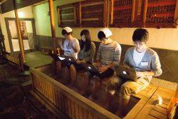 足湯に浸かりながらコードを書く参加学生たち