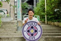 ▲渋谷のストリートでクラブのエンブレムと写るCOOの酒井翼(さかいつばさ)さん