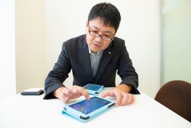"""▲自ら開発したアプリを手に、「ゲームを通じ、子どもたちに""""生きた英語""""に親しんでほしい」と語る"""