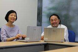 ▲2019年現在の新井聡(右)。パブリックサービス事業部の部員とのミーティング。貴重な!?笑顔の一枚!