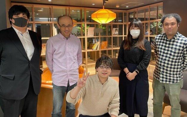▲チームメンバーに囲まれる大塚(写真中央)
